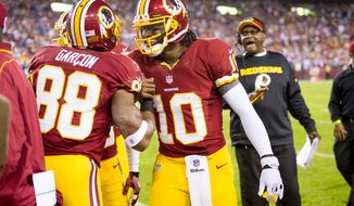 Washington Redskins quarterback Robert Griffin III (10) and Washington Redskins wide receiver Pierre Garcon (88) celebrate on the sideline after Washington Redskins wide receiver Josh Morgan (15) scores on a 13 yard run off of a fumble by Washington Redskins quarterback Robert Griffin III (10) to put the Redskins up 7-3 in the first quarter as the Washington Redskins play the New York Giants for monday night football at FedEx Field, Landover, Md., Monday, December 3, 2012. (Andrew Harnik/The Washington Times)
