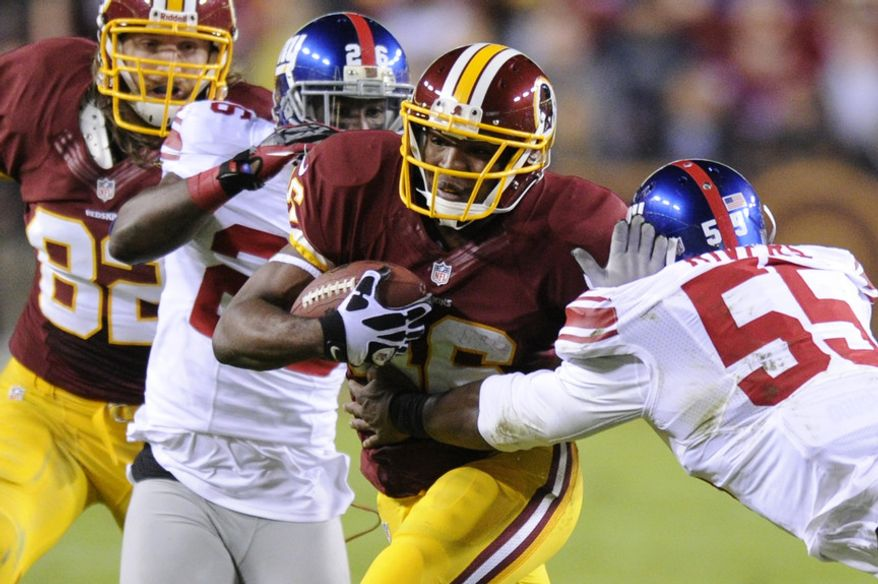 Washington Redskins running back Alfred Morris (46) runs for an 8-yard gain against New York Giants outside linebacker Keith Rivers (55) and free safety Antrel Rolle (26) in the first quarter at FedEx Field, Landover, Md., Dec. 3, 2012. (Preston Keres/Special to The Washington Times)