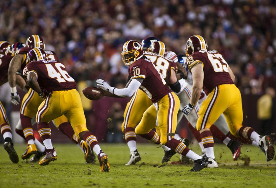 Washington Redskins quarterback Robert Griffin III (10) hands the ball off to running back Alfred Morris (46) in the first quarter against the New York Giants, Landover, Md., Monday, December 3, 2012.  (Craig Bisacre/The Washington Times)