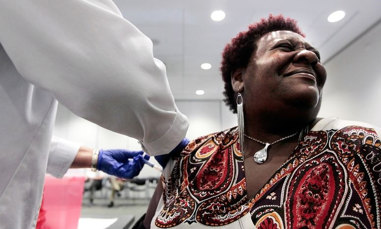**FILE** Elizabeth Saint Victor winces as she gets a free flu shot from nurse Jean Buck courtesy of Baptist Healthcare at the Central Library in Memphis, Tenn., on Oct. 30, 2012. (Associated Press/The Commercial Appeal)