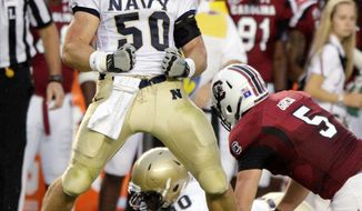 Navy linebacker Brye French, left, celebrates sacking South Carolina quarterback Stephen Garcia, right, during the first half of an NCAA college football game, Saturday, Sept. 17, 2011, at Williams-Brice Stadium, in Columbia, S.C. (AP Photo/Brett Flashnick)