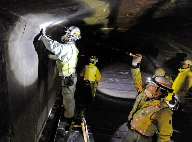 Workers inspect the structure inside the 5.3-mile Enasan Tunnel on the Chuo Expressway in Achimura, Nagano Prefecture, in central Japan, on Monday. Concrete ceiling panels fell onto moving vehicles deep inside another tunnel on the same expressway Sunday. Nine people died. (Associated Press)