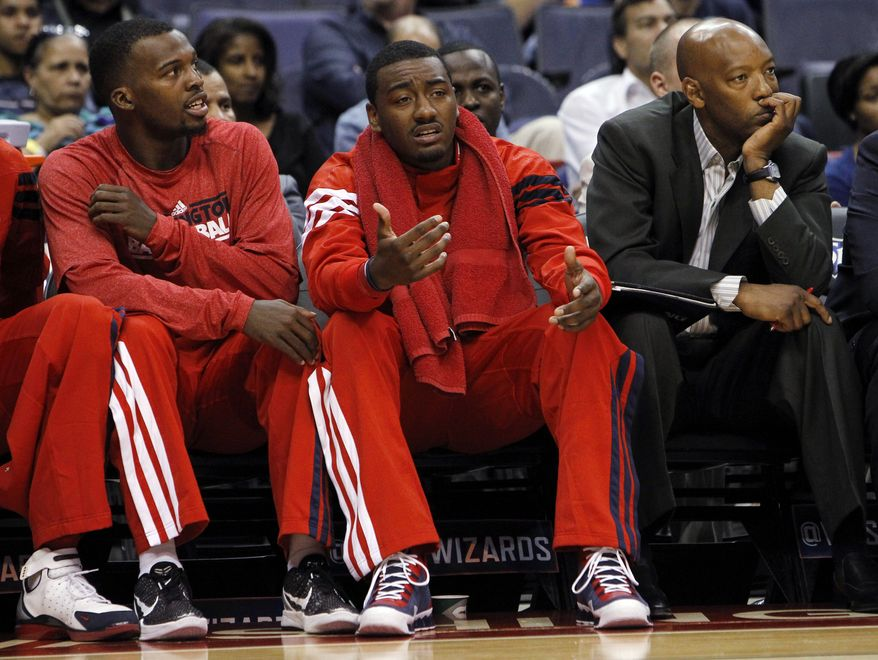 Washington Wizards guard John Wall, center, pleads with an official as he sits with guard Shelvin Mack, left, and assistant coach Sam Cassell, right, on the bench during the third quarter of an NBA preseason basketball game against the New York Knicks in Washington, Thursday, Oct. 11, 2012. The Knicks defeated the Wizards 108-101. (AP Photo/Ann Heisenfelt)