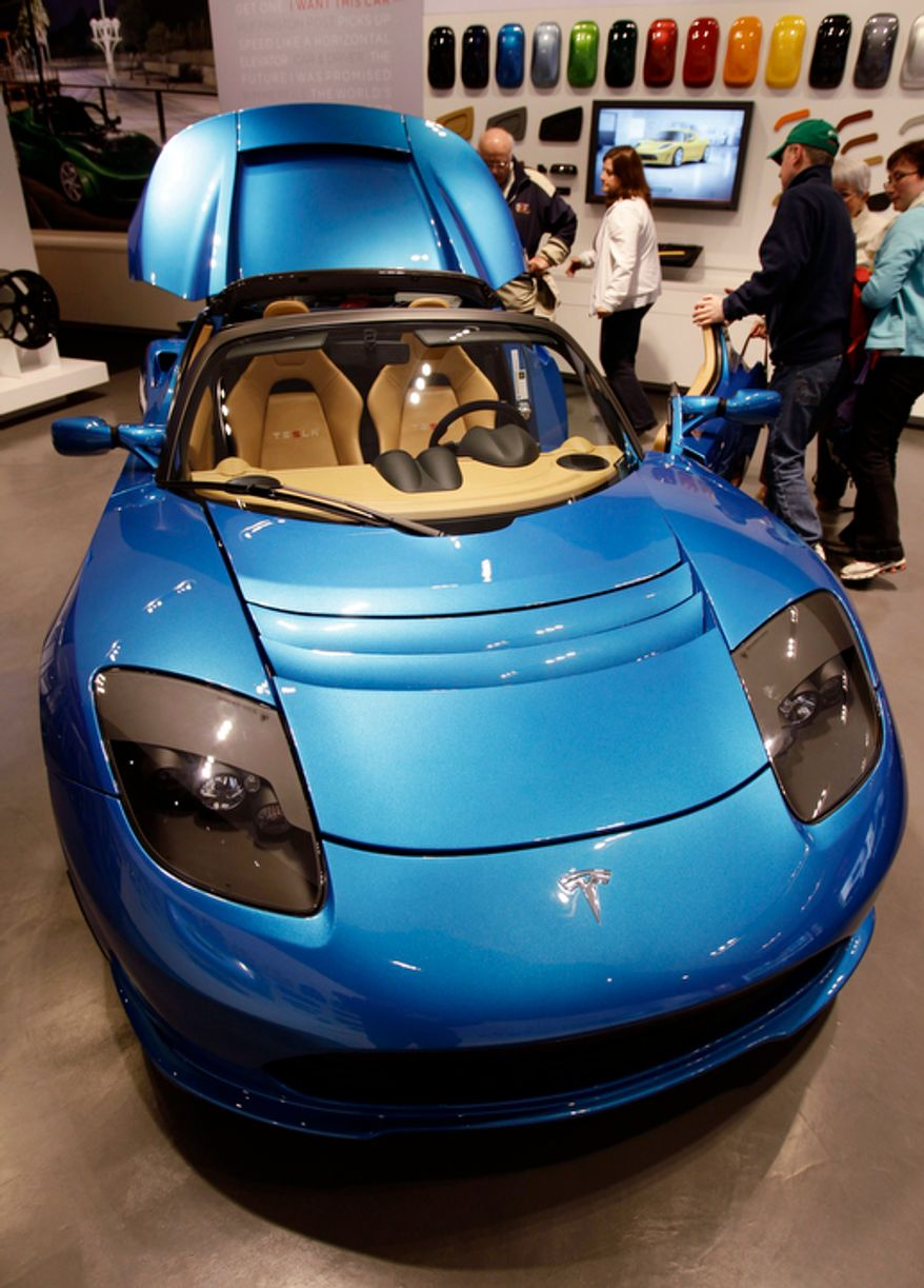 **FILE** People look at electric car Tesla Motors vehicle at a showroom in San Jose, Calif., on May 25, 2011. (Associated Press)