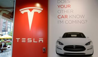 **FILE** A sign is shown inside of electric car maker Tesla Motors showroom in San Jose, Calif., on May 25, 2011. (Associated Press)