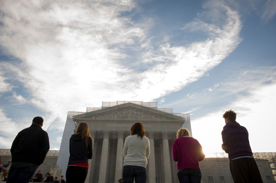 As the sun rises over the U.S. Supreme Court, people stand in silent prayer on the steps in the hour before the justices return to the bench for another term on Monday, Oct. 1, 2012. (Rod Lamkey Jr./The Washington Times)