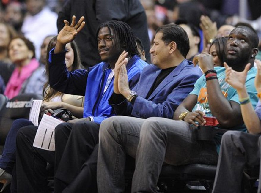 Washington Redskins quarterback Robert Griffin III waves as he attends an NBA game between the Washington Wizards and the Miami Heat, Tuesday, Dec. 4, 2012, in Washington. (AP Photo/Nick Wass)