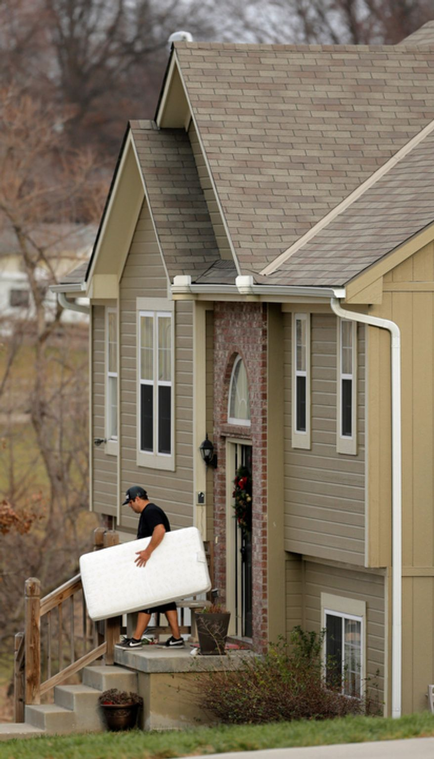 An unidentified man carries items out of a Kansas City home shared by Kansas City Chiefs linebacker Jovan Belcher and his girlfriend Kasandra Perkins on Dec. 3, 2012. Belcher killed Perkins and himself two days earlier. (Associated Press)