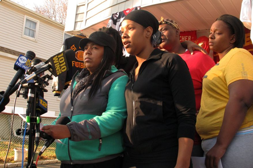 Yamiesse Lawrence (left) and Quaresha Boston (center), a cousin and niece, respectively, of Kansas City Chiefs linebacker Jovan Belcher, read a statement to the media on Dec. 3, 2012, in West Babylon, N.Y. Kansas City, Mo., police said Belcher shot and killed his girlfriend and then committed suicide on Dec. 1. In the rear are Belcher's sisters Charmaine Shepherd (second from right) and Jeanine Shepherd. (Associated Press)