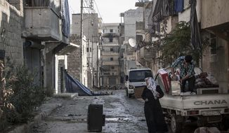 Residents of Aleppo, Syria, collect their belongings after their home was damaged in heavy fighting between Free Syrian Army fighters and government forces on Sunday, Dec. 2, 2012. (AP Photo/Narciso Contreras)