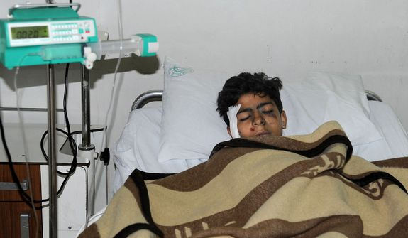 An injured Syrian student lies at a hospital bed after he was wounded when a mortar hit the al-Batiha school in al-Wafideen camp, about 25 kilometers (15 miles) northeast of Damascus, Syria, on Dec. 4, 2012. The mortar slammed into a ninth-grade classroom, killing 29 students and a teacher, according to state media, as the civil war closed in on President Bashar Assad's seat of power. (Associated Press/SANA)