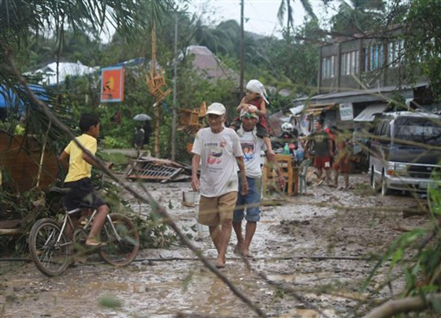Residents walk back to their homes after Typhoon Bopha made landfall in Compostela Valley in southeastern Philippines Tuesday Dec. 4, 2012. Typhoon Bopha (local name Pablo), one of the strongest typhoons to hit the Philippines this year, barreled across the country's south on Tuesday, killing at least 40 people and forcing more than 50,000 to flee from inundated villages. (AP Photo/Karlos Manlupig)