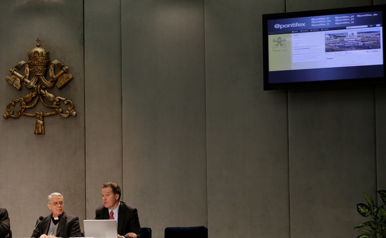 Father Federico Lombardi (left), the Vatican's spokesman, and Vatican communications adviser Greg Burke present Pope Benedict XVI's Twitter Web page (top right) to journalists at the Vatican Press Hall on Monday, Dec. 3, 2012. (AP Photo/Gregorio Borgia)