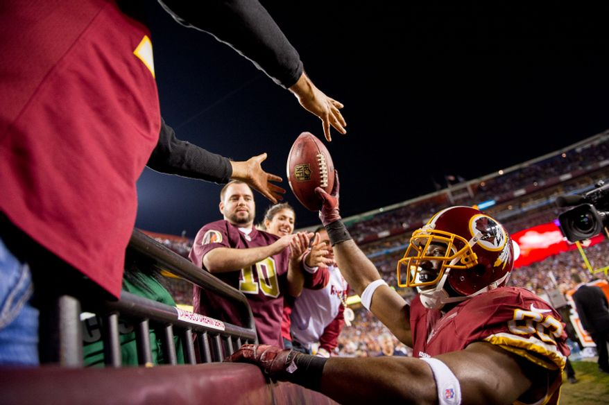 Washington Redskins wide receiver Pierre Garcon (88) hands a fan a football after catching an 8-yard touchdown in the fourth quarter as the Washington Redskins play the New York Giants on Monday Night Football at FedEx Field, Landover, Md., Dec. 3, 2012. (Andrew Harnik/The Washington Times)