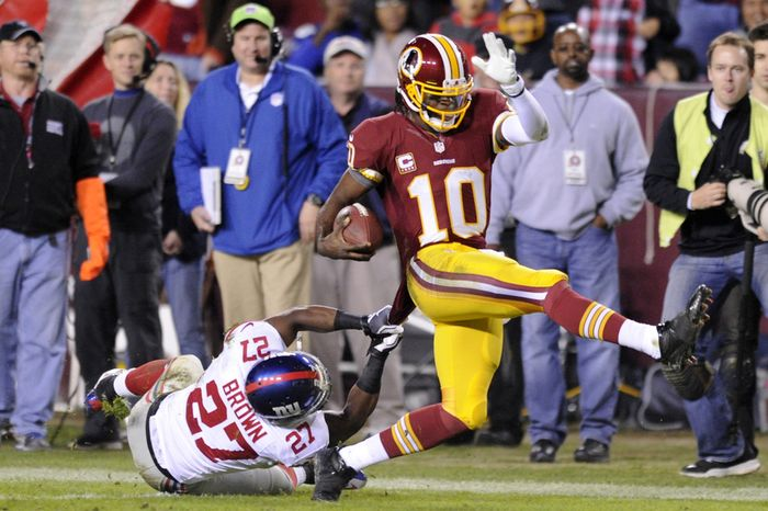 Washington Redskins quarterback Robert Griffin III (10) drags New York Giants strong safety Stevie Brown (27) to the 15-yard line at the end of a 46-yard run in the third quarter at FedEx Field, Landover, Md., Dec. 3, 2012. (Preston Keres/Special to The Washington Times)