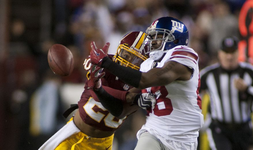Washington Redskins defensive back Cedric Griffin (20) breaks up a pass intended for New York Giants wide receiver Hakeem Nicks (88) in the first quarter, Landover, Md., Monday, Dec. 3, 2012.  (Craig Bisacre/The Washington Times)