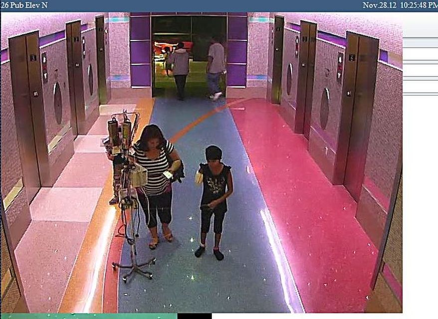 A hospital surveillance photo released by the Phoenix Police Department on Monday, Dec. 3, 2012, shows a woman with her 11-year-old daughter, a leukemia patient who had her arm amputated and a heart catheter inserted because of an infection. Authorities say the woman inexplicably took the girl from the hospital last week. (AP Photo/Phoenix Police Department)