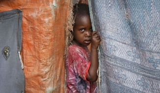 **FILE** A Somali internally-displaced child looks out from her family's makeshift home in Maslah camp on the outskirts of Mogadishu, Somalia, on Nov. 29, 2012. (Associated Press)