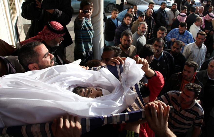 Syrians and Jordanians carry the body of Moath al-Rawashdy, 30, who was killed by Syrian forces shelling, during his funeral procession in Ramtha City, north of Amman, Jordan, on Sunday, Dec. 2, 2012. Al-Rawashdy was killed in Tafas village, in the Syrian city of Daraa, on Saturday, Dec. 1, 2012. (AP Photo/Mohammad Hannon)