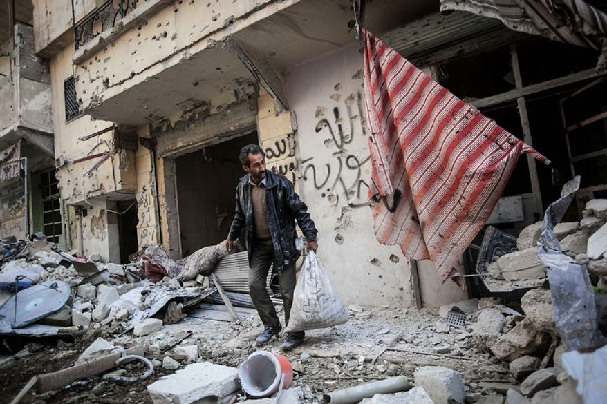 A man collects his belongings after his home was damaged in heavy fighting between Free Syrian Army fighters and government forces in Aleppo, Syria, on Sunday, Dec. 2, 2012. (AP Photo/Narciso Contreras)