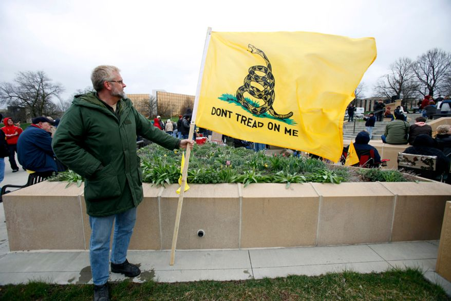 A tea party supporter holds a Don't Tread on Me flag during a rally on Saturday, April 16, 2011, at the Statehouse in Des Moines, Iowa. (AP Photo/Charlie Neibergall)