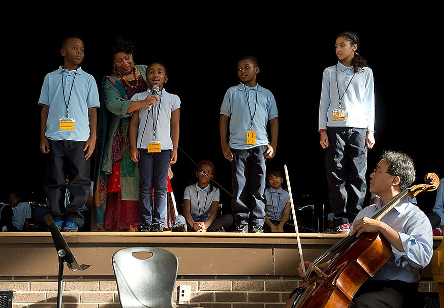 """World renowned cellist Yo Yo Ma, right, looks on as Savoy Elementary School students (from left) Kevon Gordon, Jionni Anderson, Anton Gamble and Tanaysia Smith perform a poem called """"We are Unique"""" that Mr. Ma would accompany at varying points during a performance at the school on Tuesday, Dec. 4, 2012. (Barbara L. Salisbury/The Washington Times)"""