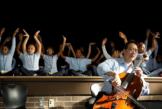 """Savoy Elementary School students stretch like swans while world renowned cellist Yo Yo Ma plays """"The Swan"""" during a performance at the Southeast Washington, D.C. school on Tuesday, Dec. 4, 2012. The cellist came to the school with another artist, Damian Woetzel, who used to dance with the New York City Ballet, to run a small private workshop with some of the children as part of the school's Innovtive Schedule for the Arts, which integrates the arts into their everyday school activities. (Barbara L. Salisbury/The Washington Times)"""