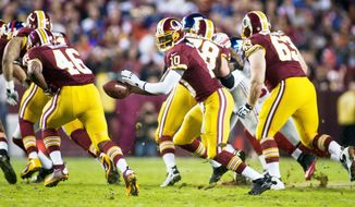 Executing the offense out of the pistol formation gives Redskins quarterback Robert Griffin III (10) multiple options for attacking a defense. (Craig Bisacre/The Washington Times)