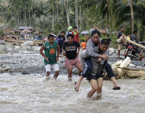 Filipinos cross a river in the flash-flood-hit village of Andap in the Compostela Valley in the southern Philippines on Wednesday, Dec. 5, 2012. Typhoon Bopha, one of the strongest typhoons to hit the country this year, barreled across the nation's south on Tuesday, killing scores of people while triggering landslides and flooding and cutting off power in two entire provinces. (AP Photo/Bullit Marquez)