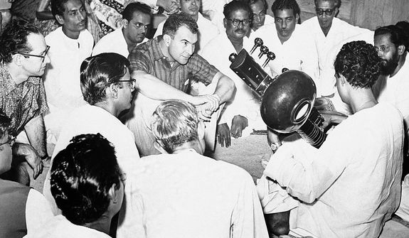 Jazz musicians, Dave Brubeck, center, and Paul Desmond, left, listen intently to Indian musicians performing on the Sitar following their performance, April, 1958, Bombay, India. (AP Photo)