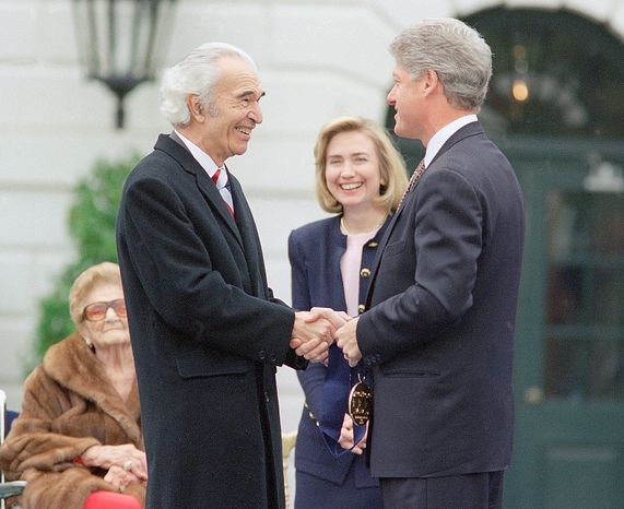 President Bill Clinton, right, shakes hands with jazz musician and composer Dave Brubeck during the 1994 National Medals of Arts ceremony at the White House, Friday, Oct. 14, 1994, Washington DC. The President presented Brubeck and others with at the 1994 National Medals of Arts. First lady Hillary Rodham Clinton looks on at center. Woman on far left is unidentified. (AP Photo/Joe Marquette)