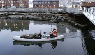 Michael Richard Smith pilots his canoe in the Boston Harbor on Dec. 4, 2012. The 49-year-old Maine native said he's been paddling the waters of metro Boston since at least late summer with all of his possessions aboard a 14-foot, 40-year-old aluminum canoe that he patches with duct tape when necessary. (Associated Press)