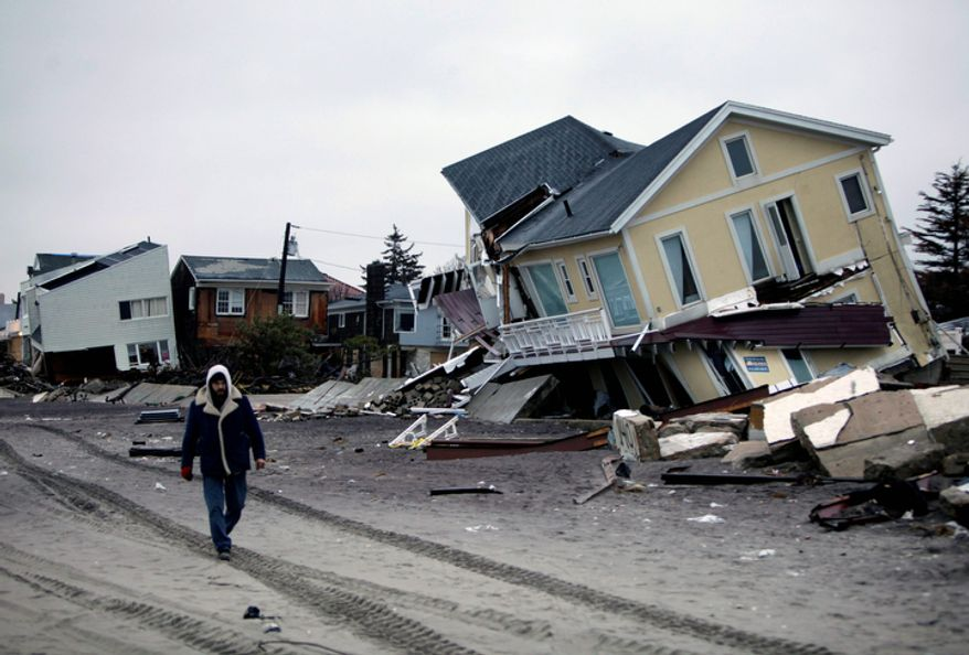 In this Tuesday, Nov. 27, 2012 file photo, a man walks past destroyed homes on the Rockaway Peninsula in Queens, New York. Delegates from nearly 200 countries are meeting in the Qatari capital of Doha to discuss ways slowing climate change, including by cutting emissions of greenhouse gases that scientists say are warming the planet, melting ice caps, raising sea levels, and changing rainfall patterns with impacts on floods and droughts. (AP Photo/Seth Wenig, File)