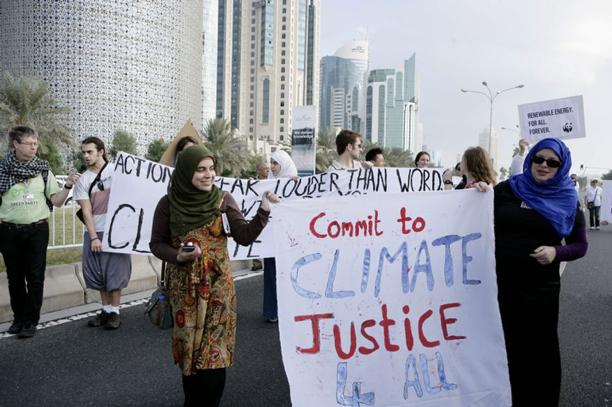 """**FILE** Qatari women activists holding a banner reading """"commit to climate justice 4 all"""" as they march with local and international activists march to demand urgent action to address climate change at the U.N. climate talks in Doha, Qatar, on Dec. 1, 2012. (Associated Press)"""