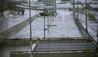 This Oct. 30, 2012 file photo shows water reaching the street level of the flooded Battery Park Underpass in New York. (AP Photo/ Louis Lanzano, File)