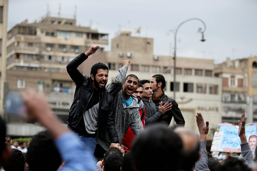 Egyptian protesters chant anti Muslim Brotherhood slogans outside the presidential palace, in Cairo, Egypt, Wednesday, Dec. 5, 2012. Supporters of President Mohammed Morsi and opponents clashed outside the presidential palace.  (AP Photo/Hassan Ammar)