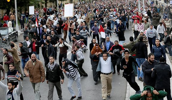 Egyptian President Mohammed Morsi's supporters clash with opponents, not pictured, outside the presidential palace, in Cairo, Egypt, Wednesday, Dec. 5, 2012.  (AP Photo/Hassan Ammar)
