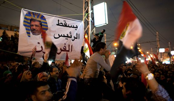 "Egyptian protesters carry national flags and chant slogans against the Muslim Brotherhood during a rally Dec. 4, 2012, in front of the presidential palace in Cairo. Tensions grew over Islamist President Mohammed Morsi's seizure of nearly unrestricted powers and a draft constitution hurriedly adopted by his allies. Arabic on the banner reads, ""down with the pharaoh president."" (Associated Press)"