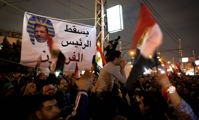 """Egyptian protesters carry national flags and chant slogans against the Muslim Brotherhood during a rally Dec. 4, 2012, in front of the presidential palace in Cairo. Tensions grew over Islamist President Mohammed Morsi's seizure of nearly unrestricted powers and a draft constitution hurriedly adopted by his allies. Arabic on the banner reads, """"down with the pharaoh president."""" (Associated Press)"""