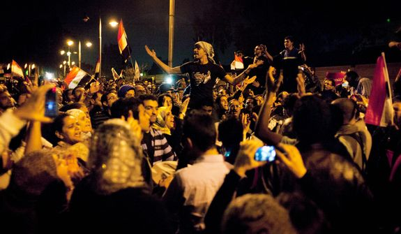 Egyptian protesters chant slogans against the Muslim Brotherhood during a rally Dec. 4, 2012, in front of the presidential palace in Cairo. (Associated Press)