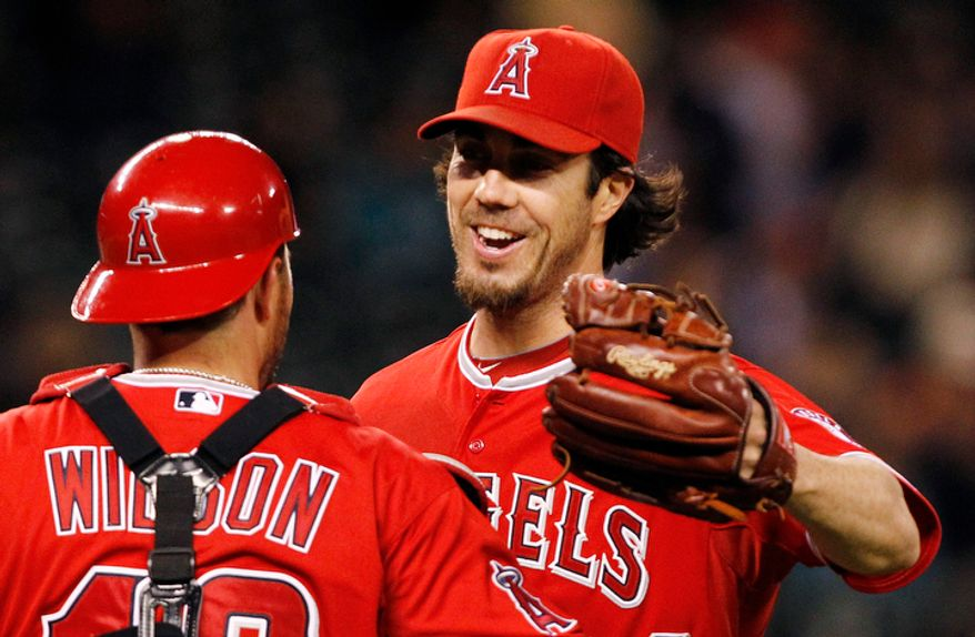 Los Angeles Angels starting pitcher Dan Haren (24) shares congratulations with catcher Bobby Wilson after the team beat the Seattle Mariners in a baseball game Thursday, May 24, 2012, in Seattle. The Angels won 3-0. (AP Photo/Elaine Thompson)