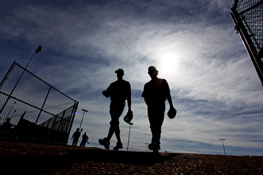 Los Angeles Angels' LaTroy Hawkins, left, and Dan Haren make their way to a practice field during a spring training baseball workout, Wednesday, Feb. 22, 2012, in Tempe, Ariz. (AP Photo/Morry Gash)
