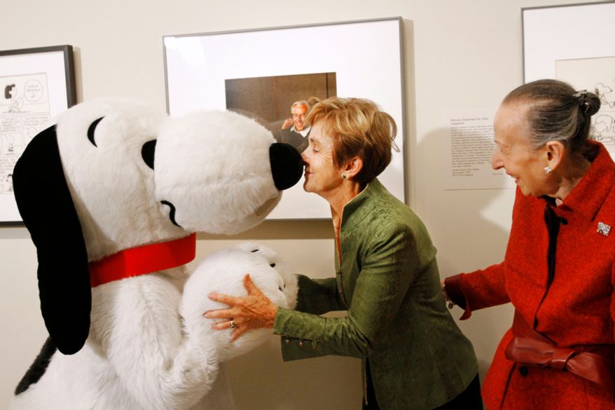 "Jean Schulz (center), widow of cartoonist Charles M. Schulz, rubs noses with Snoopy in front of a portrait of the ""Peanuts"" creator by photographer Yousuf Karsh on Friday, Oct. 1, 2010, at the National Portrait Gallery in Washington, during a ceremony in which the portrait was presented to the gallery. Estrellita Karsh, wife of the photographer, is at right. (AP Photo/Jacquelyn Martin)"
