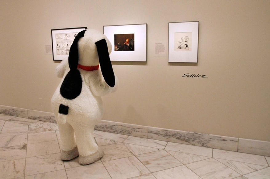 "The life-size Snoopy looks at a portrait of ""Peanuts"" creator Charles M. Schulz, by photographer Yousuf Karsh, during its installation at the National Portrait Gallery in Washington on Friday, Oct. 1, 2010. To the left and right of the portrait are drawings of Schulz's ""Peanuts"" characters. (AP Photo/Jacquelyn Martin)"