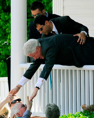 While a Secret Service agent holds onto his waist, former President Bill Clinton stretches over a porch rail and shakes hands with well-wishers during a campaign stop on Sunday, May 4, 2008, in Morganton, N.C. The former president was campaigning for his wife, Sen. Hillary Rodham Clinton, a Democratic presidential hopeful. (AP Photo/The News Herald, Jennifer Frew)