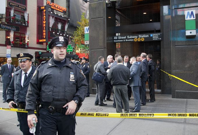 Uniformed and plainclothes police officers stand outside a New York subway station after a man was killed after being pushed into the path of a train on Dec. 3, 2012. (Associated Press)