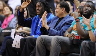 Washington Redskins quarterback Robert Griffin III waves as he attends an NBA basketball game between the Washington Wizards and the Miami Heat, Tuesday, Dec. 4, 2012, in Washington. (AP Photo/Nick Wass)