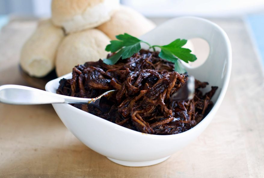 Sweet-and-tangy barbecue brisket is a delicious filler for sliders and gives you time to enjoy the holiday. (Associated Press)