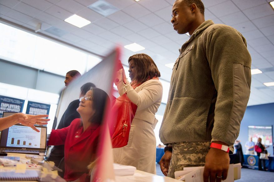 U.S. Army Staff Sgt. Ricardo Hamer, right, and his coworker U.S. Army civilian Rekisha White, second from right, talks with Washington, D.C. Area Chapter Director Karen Francis with Blue Star Families, a nonprofit that supports, connects, and empowers military families, at the U.S. Chamber of Commerce's Hiring Our Heroes hiring fair at Nationals Park in Washington on Dec. 5, 2012. While Hamer and White were at the fair to get information on joining the job hirers next time for the Army Core of Engineers, Hamer was also there to look for employment ideas for his wife. (Andrew Harnik/The Washington Times)