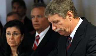Jim Letten, U.S. attorney for the Eastern District of Louisiana, announces his resignation during a news conference in New Orleans on Thursday, Dec. 6, 2012. His wife, JoAnn, is at left. (AP Photo/Gerald Herbert)